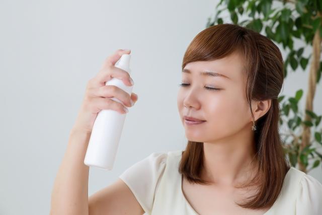 ミスト化粧水をかける女性